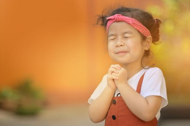 Милая азиатская маленькая девочка закрыла глаза и молиться по утрам. маленькая азиатская рука моля, руки девушки сложенная в концепции молитве для веры, духовности и вероисповедания. Premium Фотографии