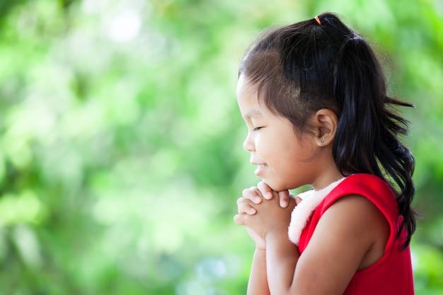 Милая азиатская маленькая девочка в рождественском платье закрыла глаза и сложила руку в молитве Premium Фотографии