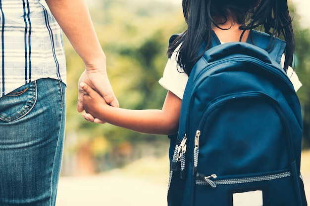 Cute asian pupil girl with backpack holding her mother hand and going to school Premium Photo