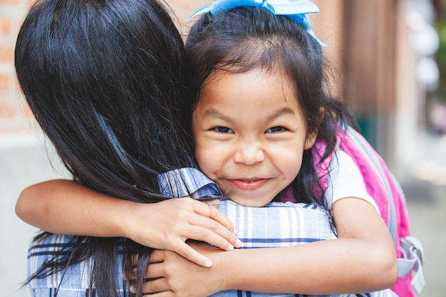 Cute asian pupil girl with backpack hugging her mother with happiness after back from school Premium Photo