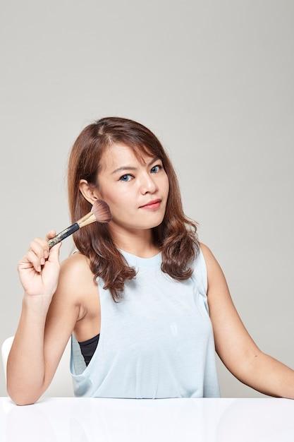 Cute Asian Teen Applying Blush Premium Photo