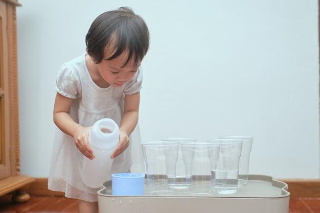 Симпатичная азиатская девочка-малышка, весело проводящая время, играя с водным столом дома, практическая жизненная деятельность дошкольного монтессори с мокрым наливанием, развитие мелкой моторики Premium Фотографии