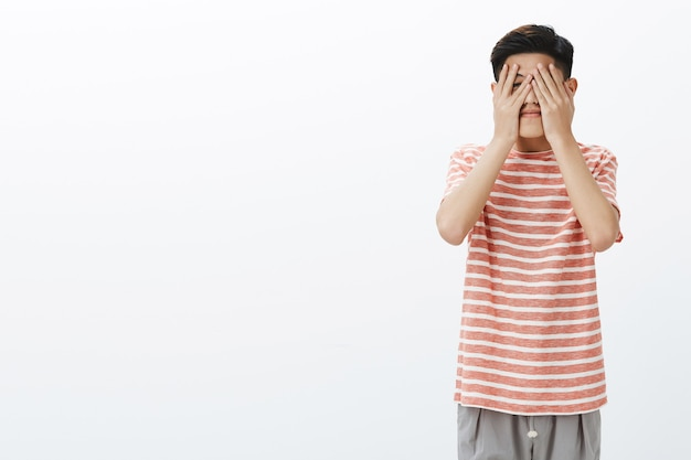 Cute asian young male student eager to see what fate prepared for him Free Photo