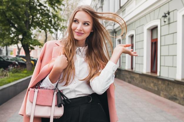 Симпатичная привлекательная стильная улыбающаяся женщина гуляет по городской улице в розовом пальто весенней модной тенденции, держащей кошелек, элегантный стиль Бесплатные Фотографии