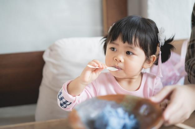 귀여운 아기와 여기 카페에서 아이스크림을 먹는 어머니 프리미엄 사진