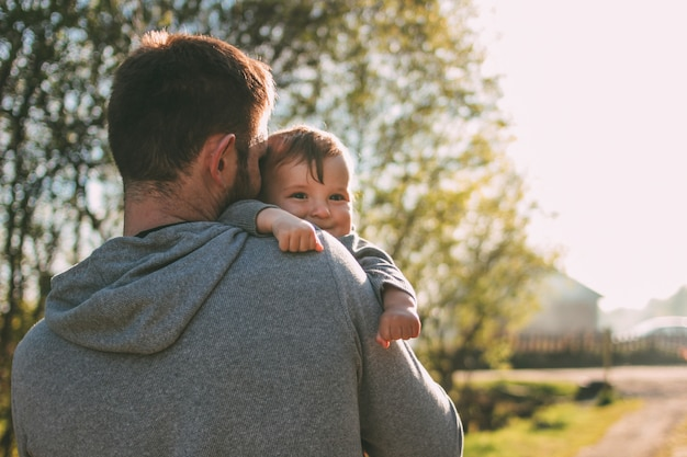 Cute baby boy on his dad shoulders walking on the village road outdoors Premium Photo