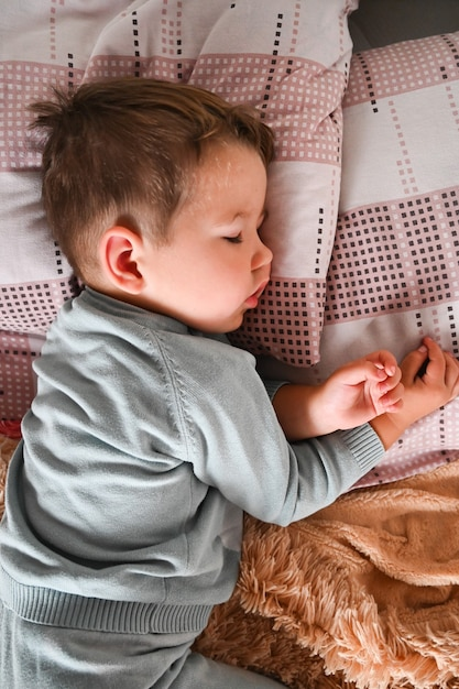 Милый мальчик спит днем. детство, кроватка. Premium Фотографии