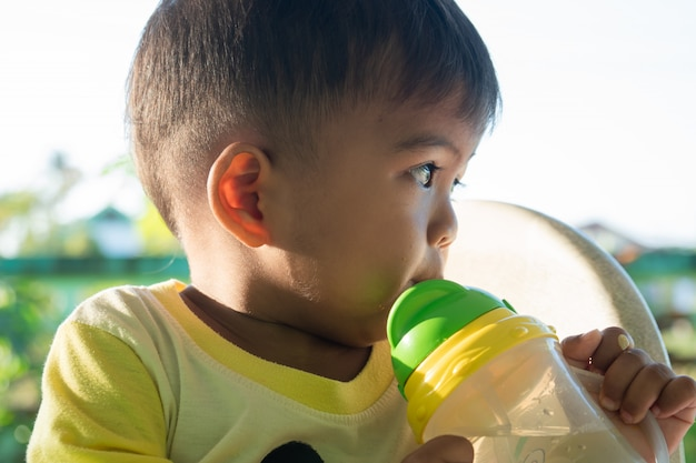 Cute baby boy sucking water from bottles Premium Photo