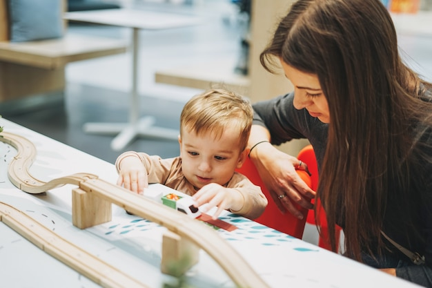 Cute baby boy toddler child with mother play with car toys in game room in the shopping mall Premium Photo