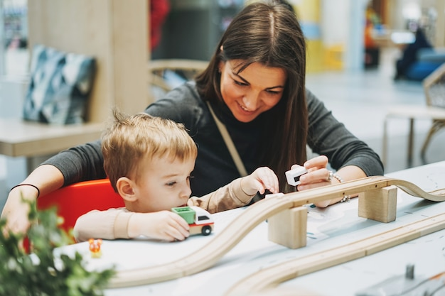 Cute baby boy toddler child with mother play with car toys in game room in shopping mall Premium Photo