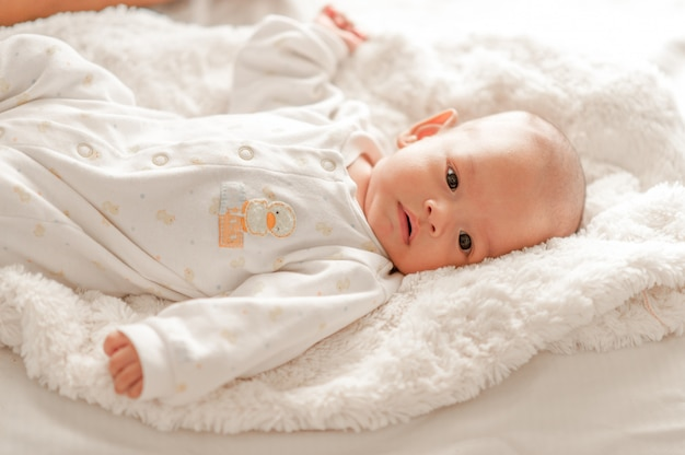 Cute baby boy in a white light bedroom newborn baby is cute. in bedding for children born - images Premium Photo