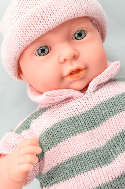 Cute baby doll for girl in knitted dress close up Premium Photo