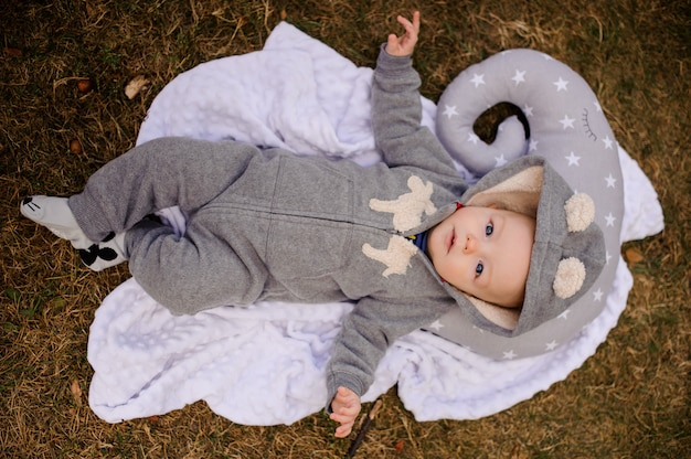 Cute baby dressed in romper with hood lying on the pillow Premium Photo