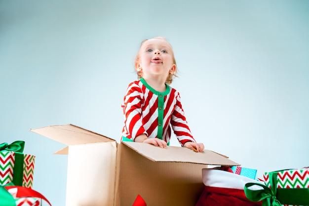 Милая девочка 1 год сидит в коробке на рождество Бесплатные Фотографии