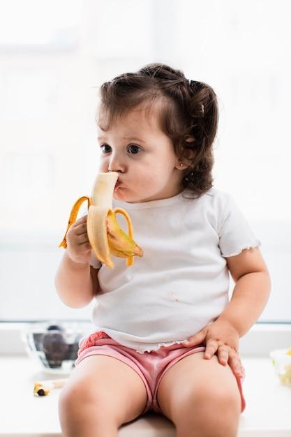 Cute baby girl eating banana Free Photo