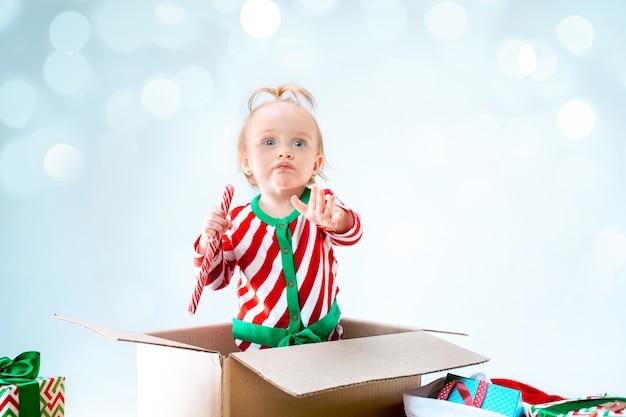 크리스마스 배경 위에 상자에 앉아 귀여운 아기 소녀. 휴일, 축하, 아이 개념 무료 사진