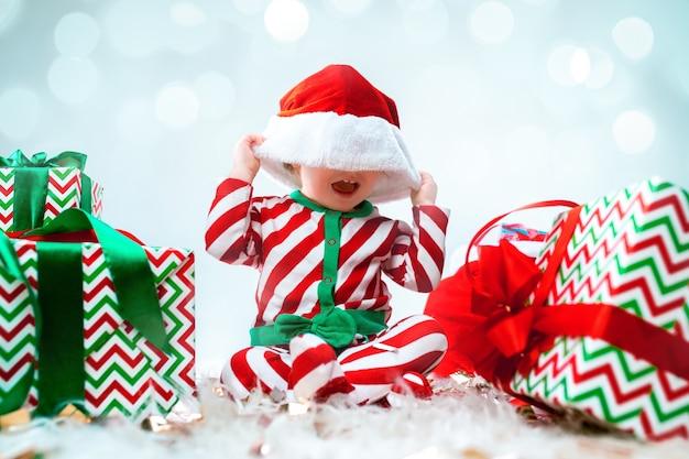 Милая девочка в шляпе санта позирует над рождественскими украшениями с подарками. сидя на полу с елочным шаром. курортный сезон. Бесплатные Фотографии