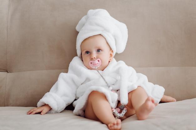 Cute baby girl in white bathrobe Free Photo