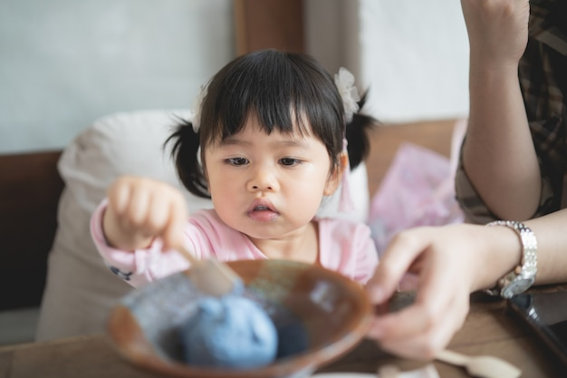Cute baby and here mother eating ice cream in the cafe Premium Photo