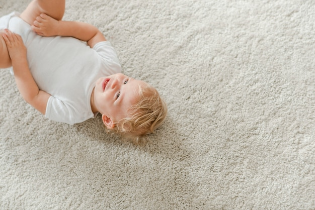Cute baby lying on the carpet Premium Photo