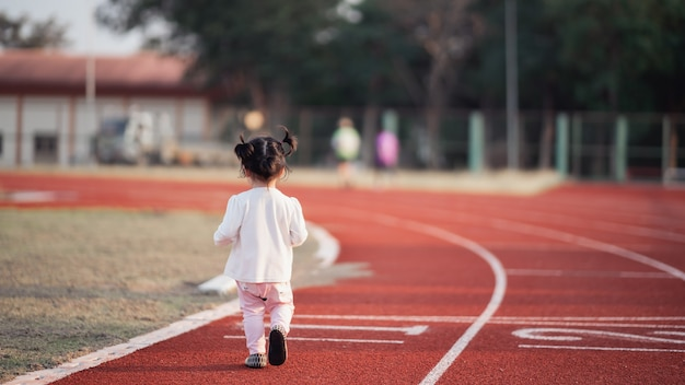 Cute baby running in the stadium Premium Photo