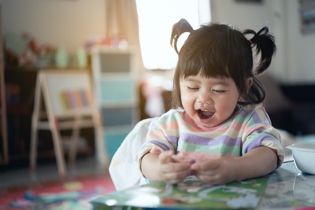 Cute baby smiling and laugh sitting on the chair in the house Premium Photo