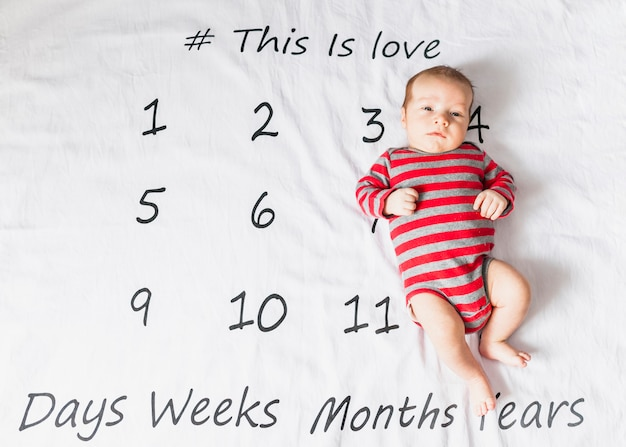 Cute baby on striped body with calendar Free Photo