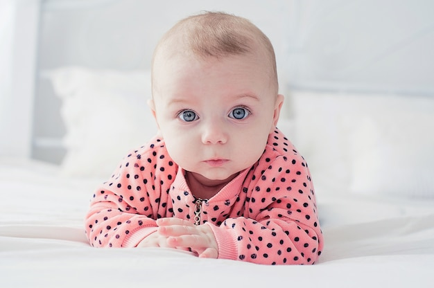 Cute baby on the white bed Premium Photo