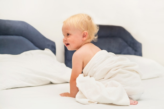 Cute baby under a white towel sits on the bed Premium Photo