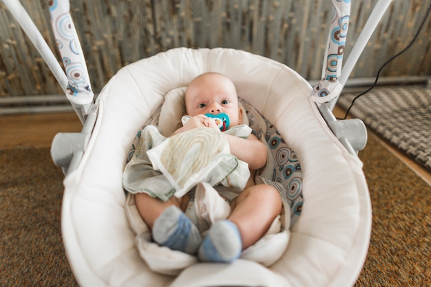 Cute baby with pacifier lying on baby carriage at home Free Photo