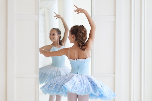 A Cute Ballerina In Ballet Costume And In Pointe Dances Near The Mirror Girl In The