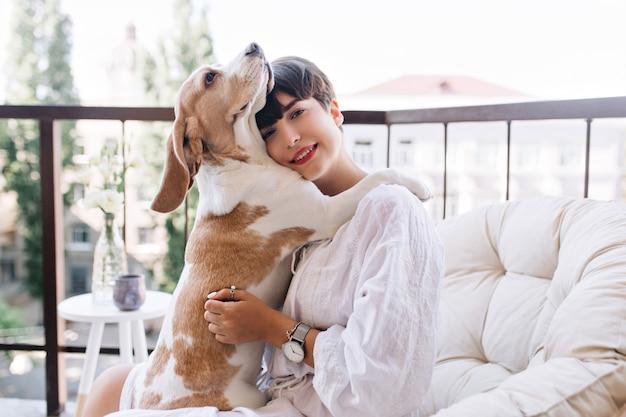 Cane beagle carino che abbraccia la ragazza dai capelli neri per esprimere fedeltà Foto Gratuite