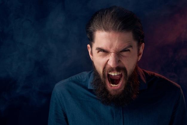 シャツのエレガントなスタイルのクローズアップ暗い背景のかわいいひげを生やした男。 Premium写真