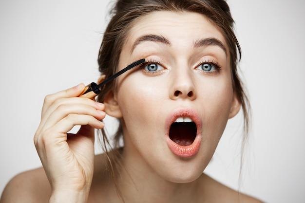 Милые красивые ресницы краски девушки при раскрытый рот смотря камеру над белой предпосылкой. красота здоровье и косметология концепции. Бесплатные Фотографии