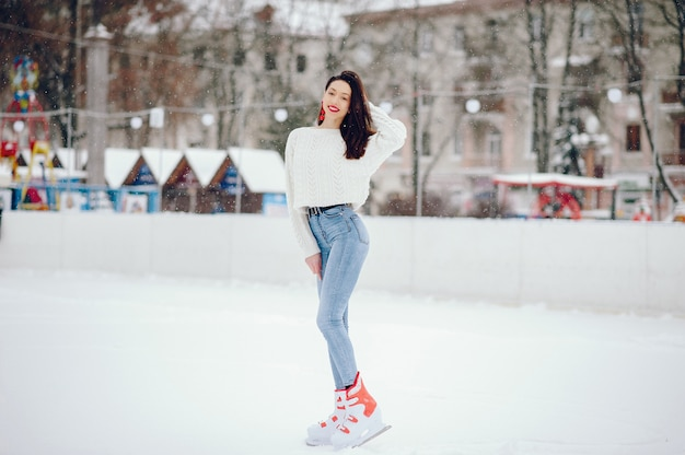 Cute and beautiful girl in a white sweater in a winter city Free Photo