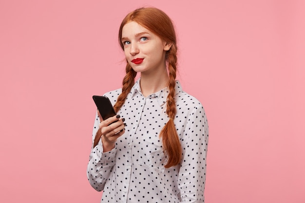 Cute beautiful red-haired girl holding a phone on her hand looks coquettishly mysteriously in the upper right corner, is thinking what to write to her boyfriend in a message, isolated on a pink Free Photo