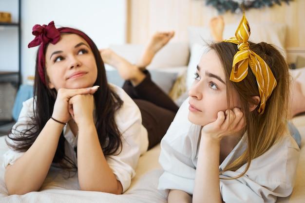 Симпатичные красивые девушки-подростки с повязками на голове лежат на диване, держатся за руки под подбородком и смотрят с задумчивым выражением лица, им скучно Бесплатные Фотографии
