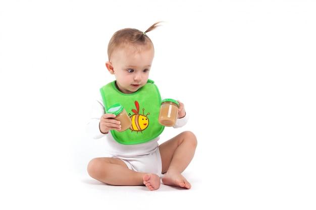 Cute beauty little girl in green bib hold baby food Premium Photo