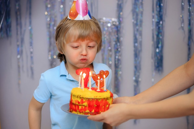 케이크를 끄고 귀여운 생일 소년 프리미엄 사진