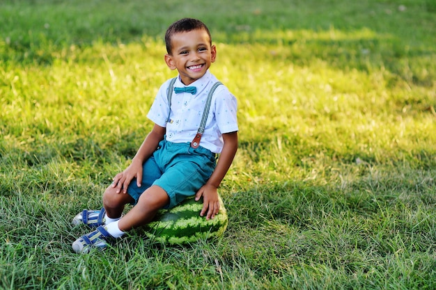 Cute black african american boy sitting on a huge watermelon and smiling on a park Premium Photo