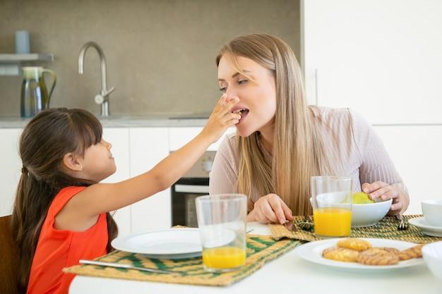 彼女の家族と一緒に朝食を食べて、試飲とかむために彼女のお母さんにクッキーを与えるかわいい黒い髪の女の子 無料写真