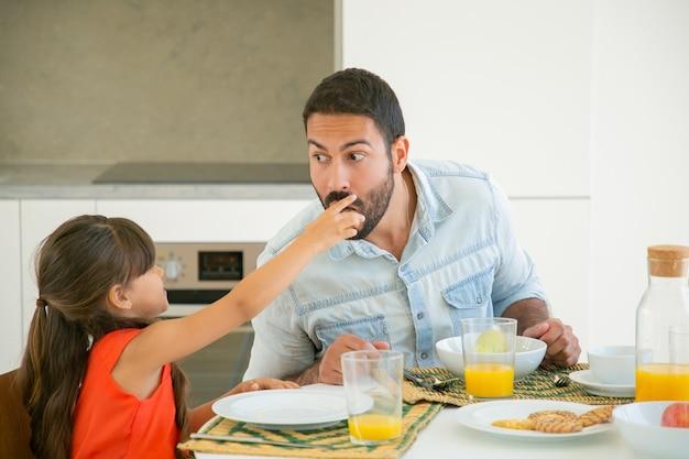 味見とかむために彼女のお父さんに食べ物のスライスを与えるかわいい黒い髪の女の子 無料写真