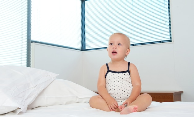 Cute blond baby sitting on bed alone Premium Photo