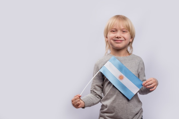 Милый белокурый мальчик держит флаг аргентины. Premium Фотографии