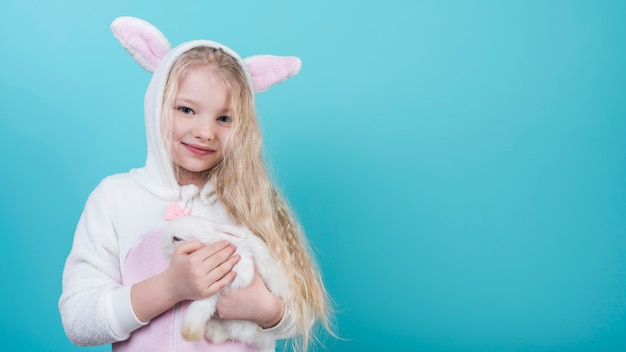 Cute blond girl in bunny ears with rabbit Free Photo