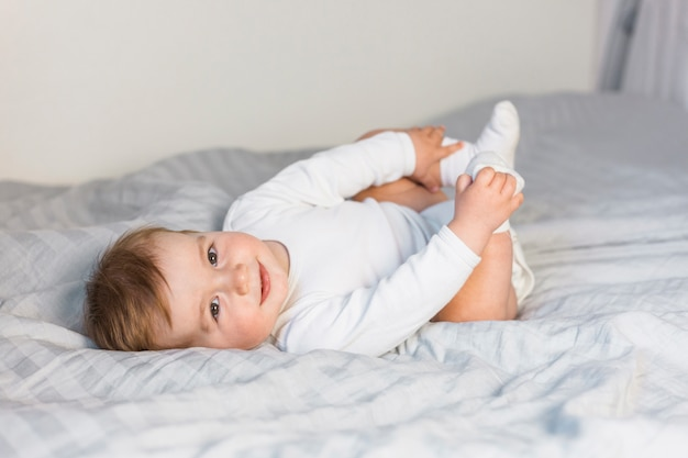 Cute blonde baby in white bed playing with feet Free Photo