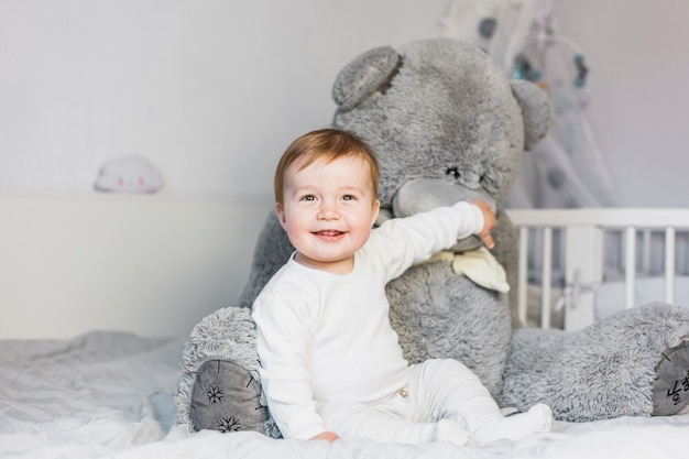 Cute blonde baby in white bed with teddy bear Free Photo