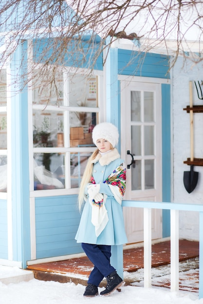 Cute blonde girl in a blue coat, white fur hat and a scarf in winter. the girl on the porch of the house. winter home. model posing on the street. the concept of winter holidays. russian painted shawl Premium Photo