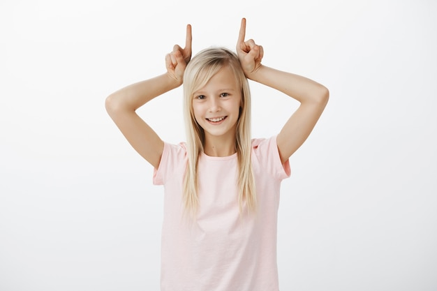 悪魔の角を示し、笑顔のかわいいブロンドの女の子 無料写真
