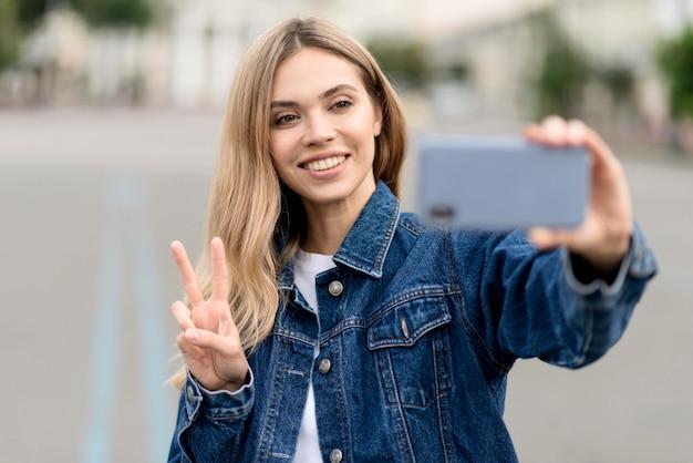 Ragazza bionda carina che cattura un segno di pace selfie Foto Gratuite
